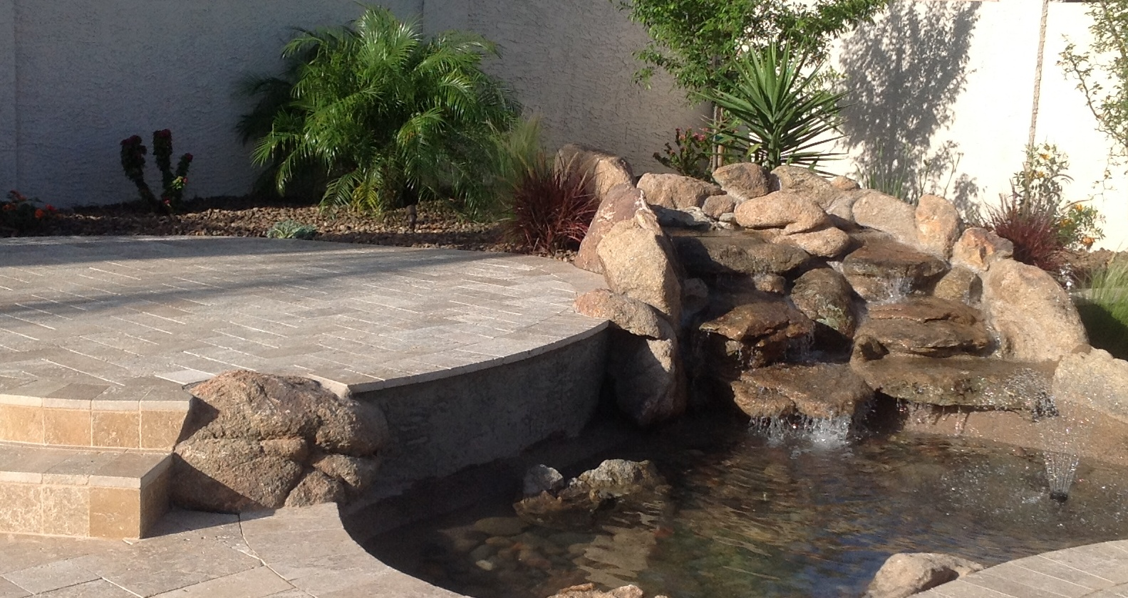 Adding waterscaping like this waterfall pond to your patio add to the backyard experience.