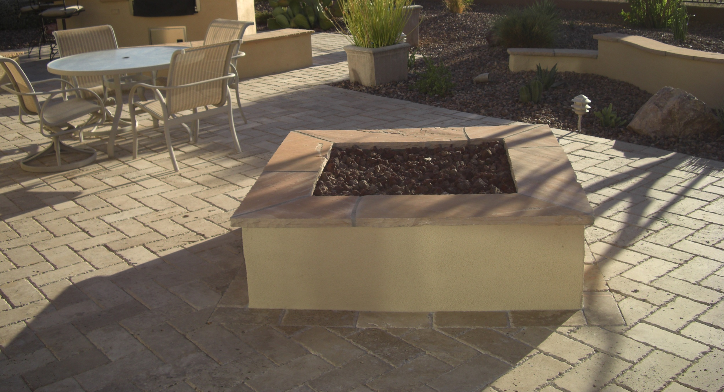 We set this custom Phoenix fire pit on an angle in the travertine pavers for greater interest. The result makes it outstanding surrounded by curved shapes in the overall landscape design.