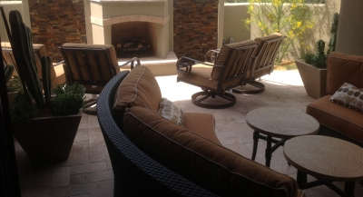 We turned this condo's entire backyard space into a gorgeous, full-featured outdoor room. Scottsdale landscaping included extending the patio with travertine pavers, erecting privacy walls, adding a stone and stucco fireplace-waterfalls combo, and a stone built-in gas grill with bar seating.