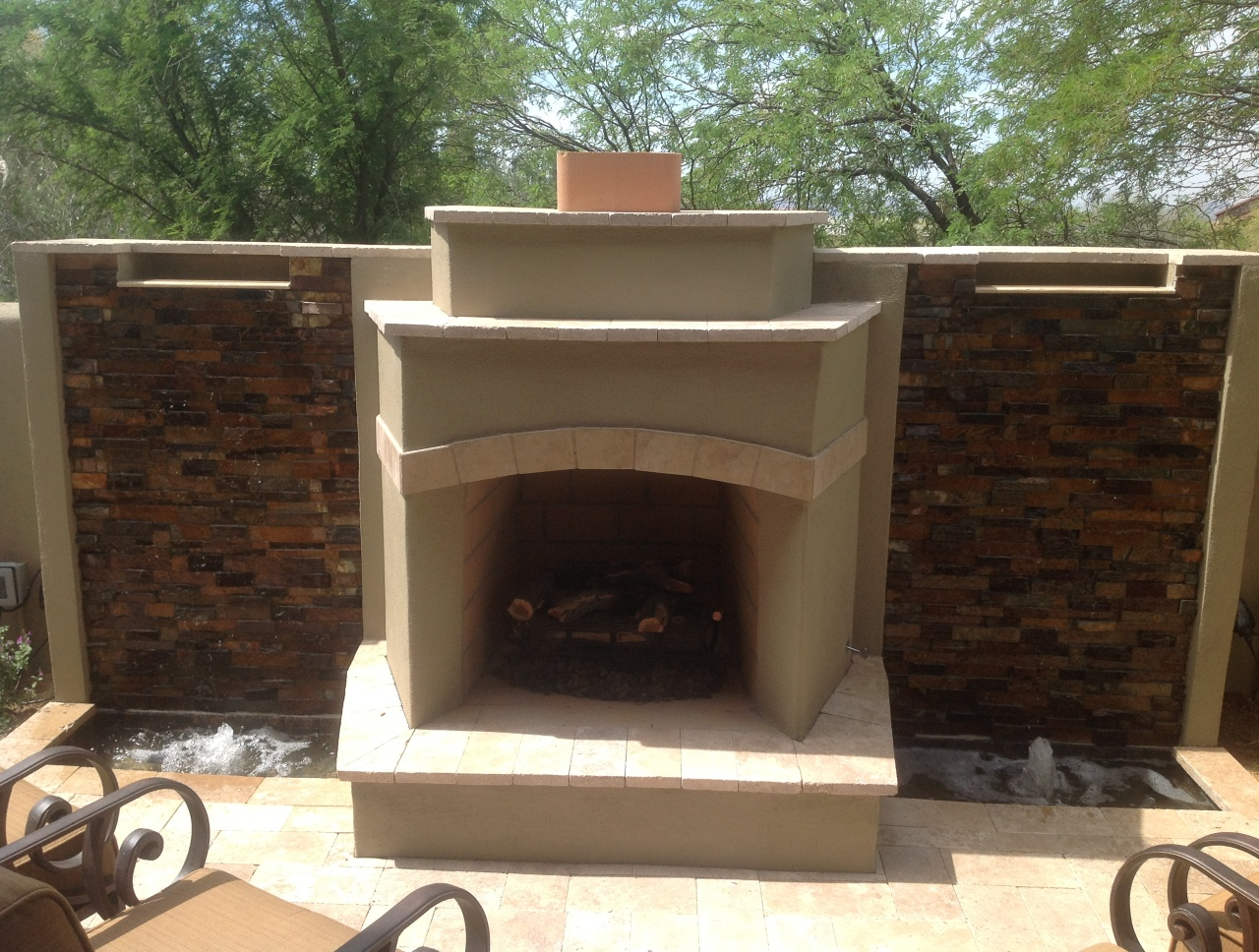 Water cascades over rich, dark stone on foth sides of this Scottsdale outdoor fireplace. The combo unit packs more assets into this small condo outdoor living space.