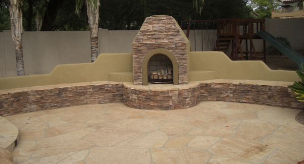 Big curving seat walls are great when entertaining large groups. Stone and stucco make great looking outdoor fireplaces. Glendale, AZ outdoor living spaces with loads of style.