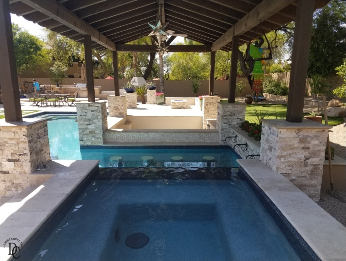 Peoria, AZ pool design features a raised spa across the fountain wall from the swim bar.