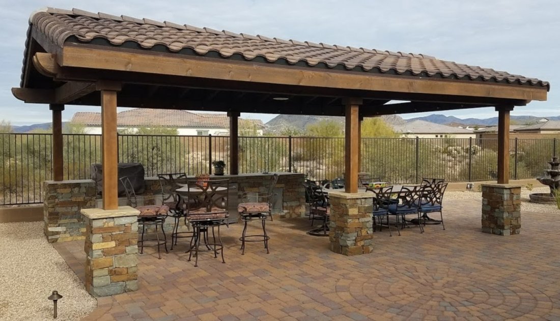 Dark brown timber support posts rise from rich stone pedestals under a classic tile patio shade roof. You best choice in comfort from shade structures. Cave Creek clients now enjoy it's cooling effect over their outdoor kitchen and dining space.