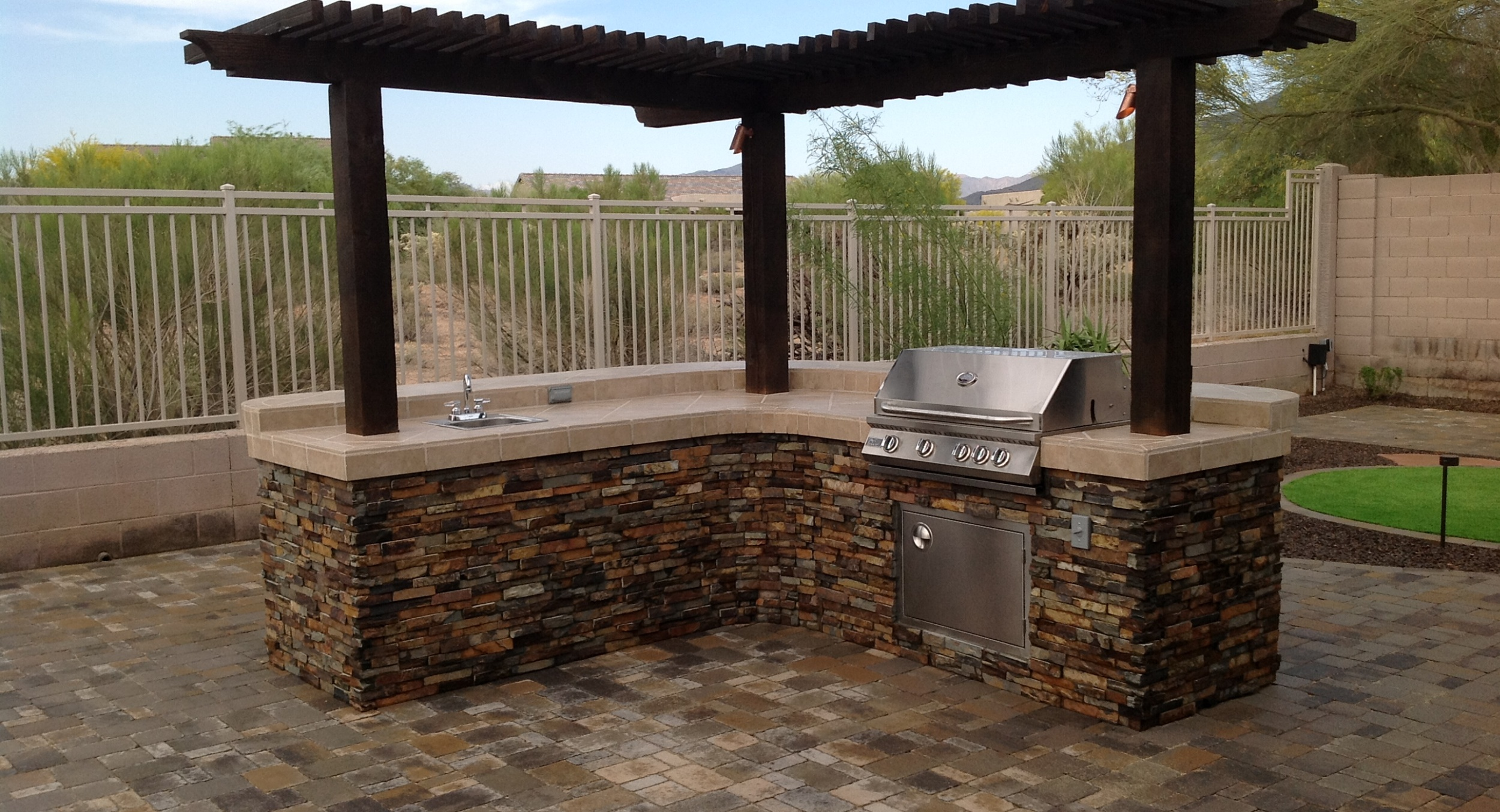 This lovely Cave Creek landscape design: has a very unique stone and tile built-in grill with a bar on the new paver patio. The island has its own attached shade pergola made from dark wood.