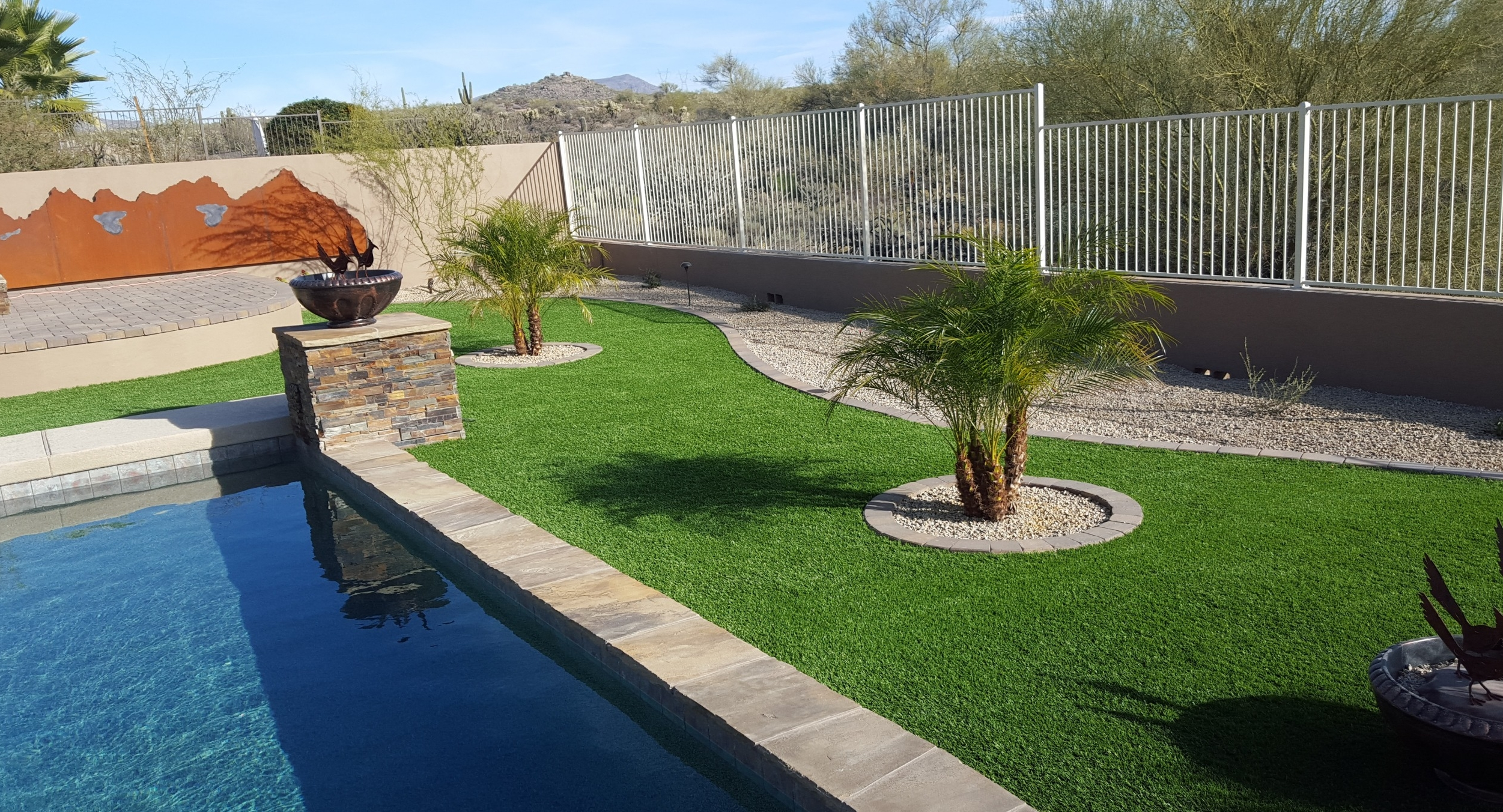 The pool area in this clients new landscaping. Phoenix, AZ low-maintenance synthetic grass brightens the space between the raised fire pit paver patio and the pools new stone pedestals and coping.