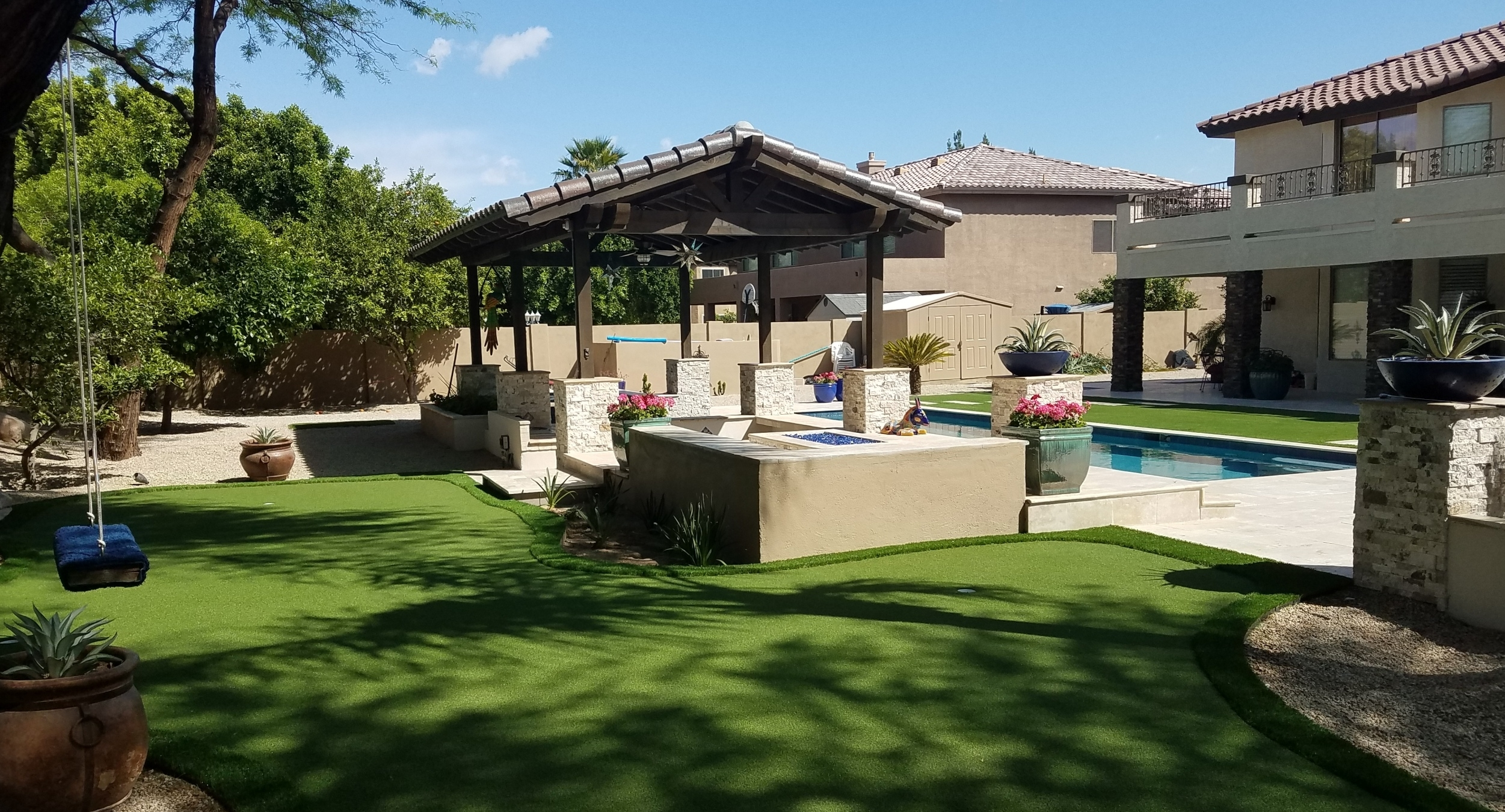 A total backyard remodel took place in the Peoria landscape design. A putting green behind the new swimming pool with a travertine patio that includes two fire pits, and several outdoor living spaces.