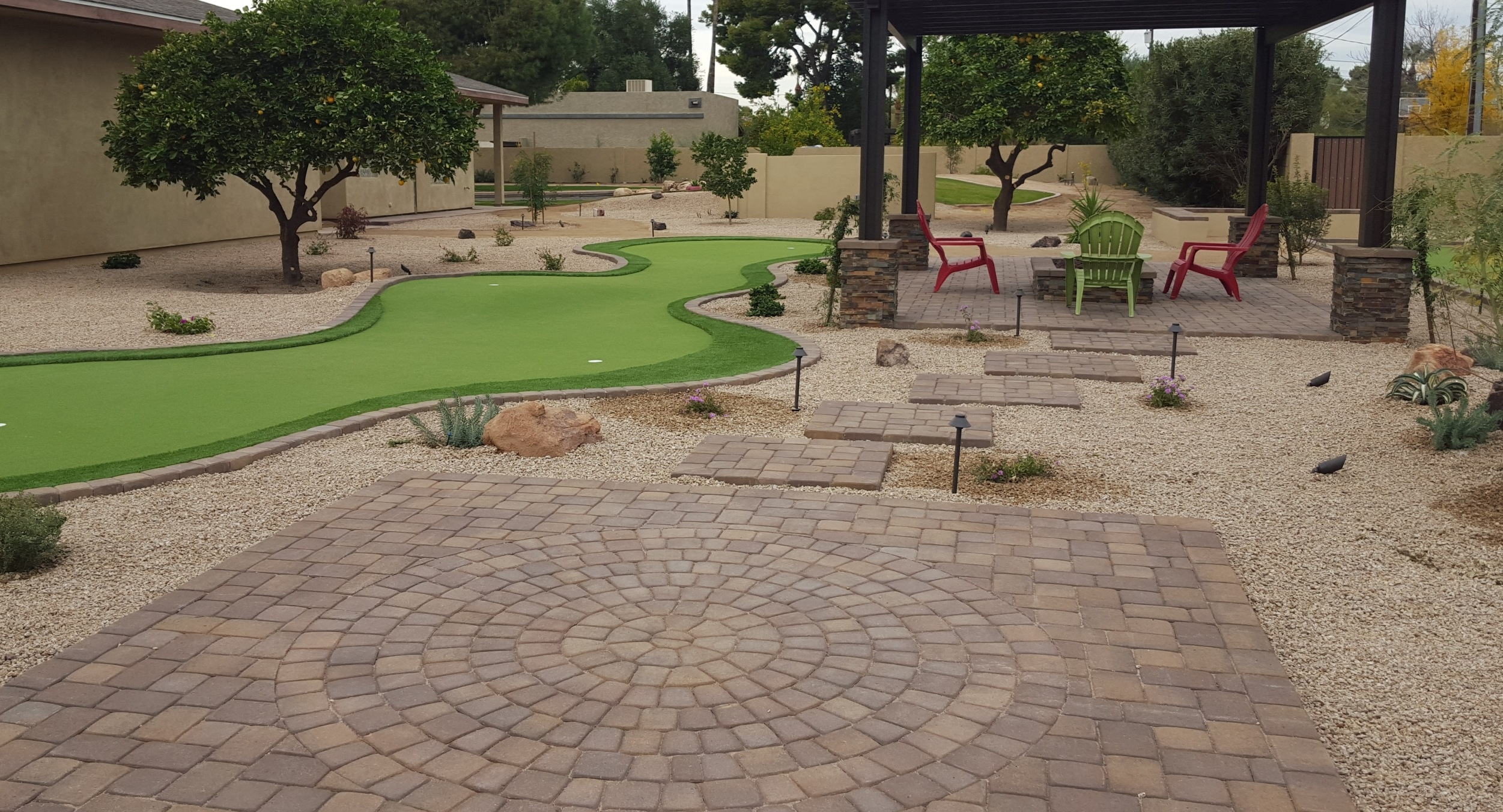 What people want in their Scottsdale or Phoenix outdoor living spaces varies. This client added a big putting green next to a pergola-shaded patio with a fire pit; useful any time of day.