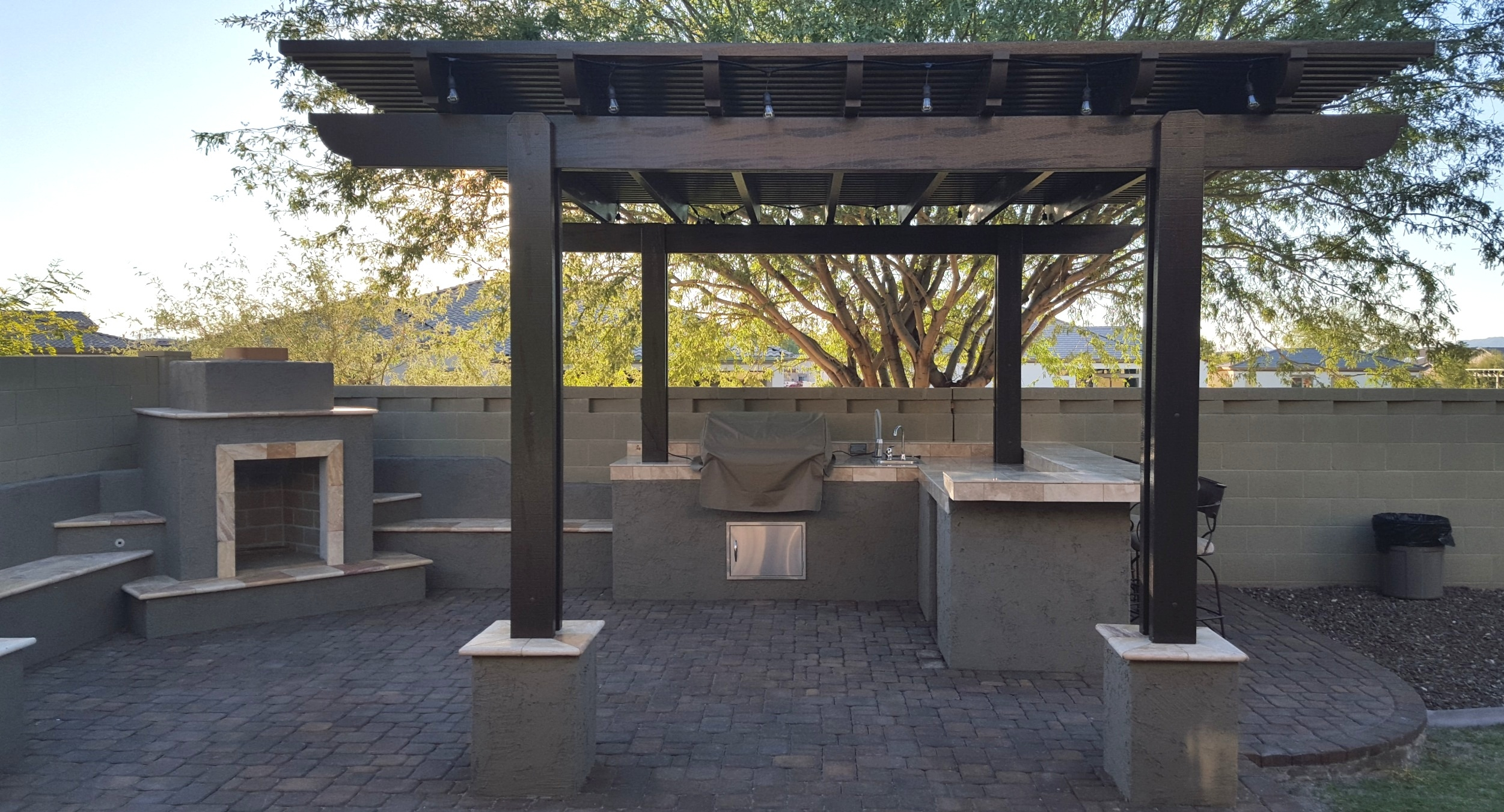 This Anthem landscape design by includes an outdoor living space with fireplace and small outdoor kitchen with a bar beneath a trellis ramada.