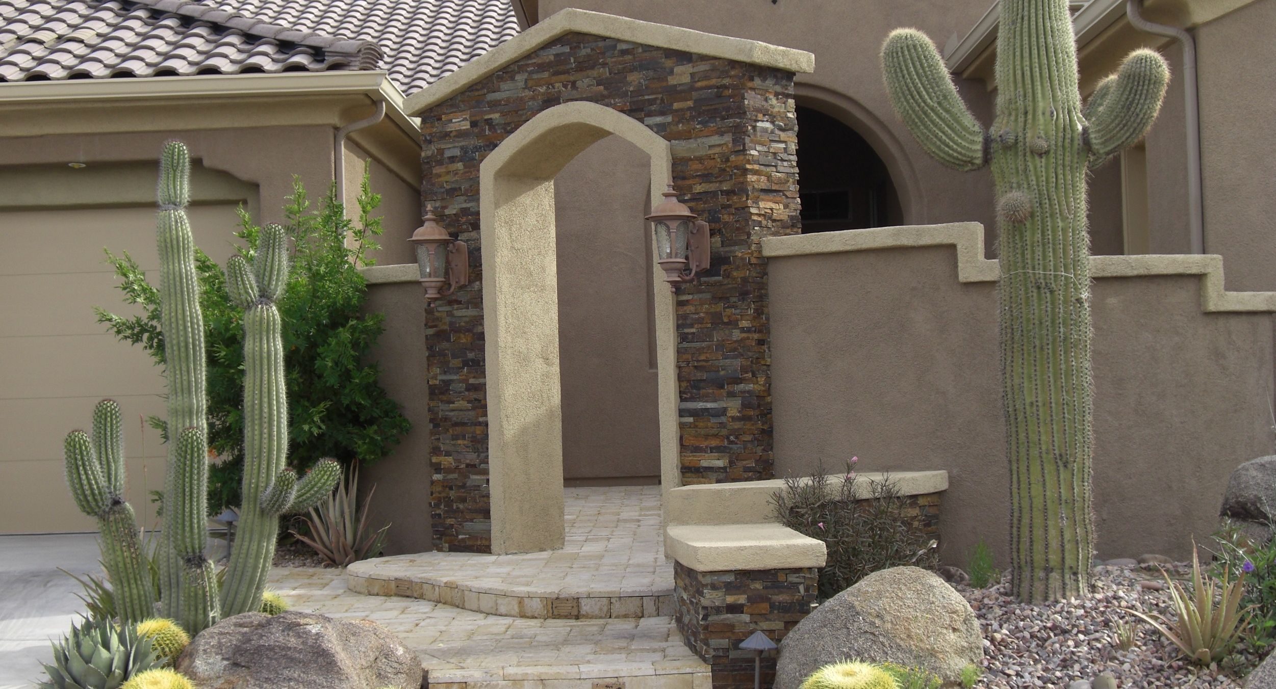 Add so much style and character to your home with courtyard landscaping, Phoenix and Scottsdale. This client chose a secluded courtyard with a sensational dark stone faced arch with a few bold cacti to set it off.