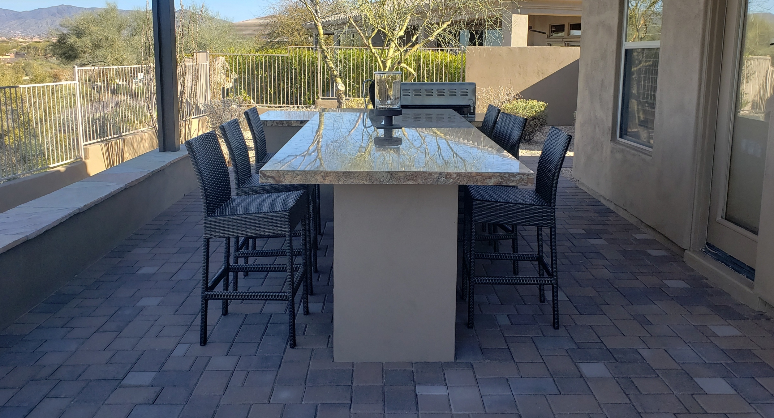 A gorgeous marble-topped outdoor bar and dining table with matching built-in gas grill by Scottsdale - Phoenix landscapers, Desert Crest LLC.