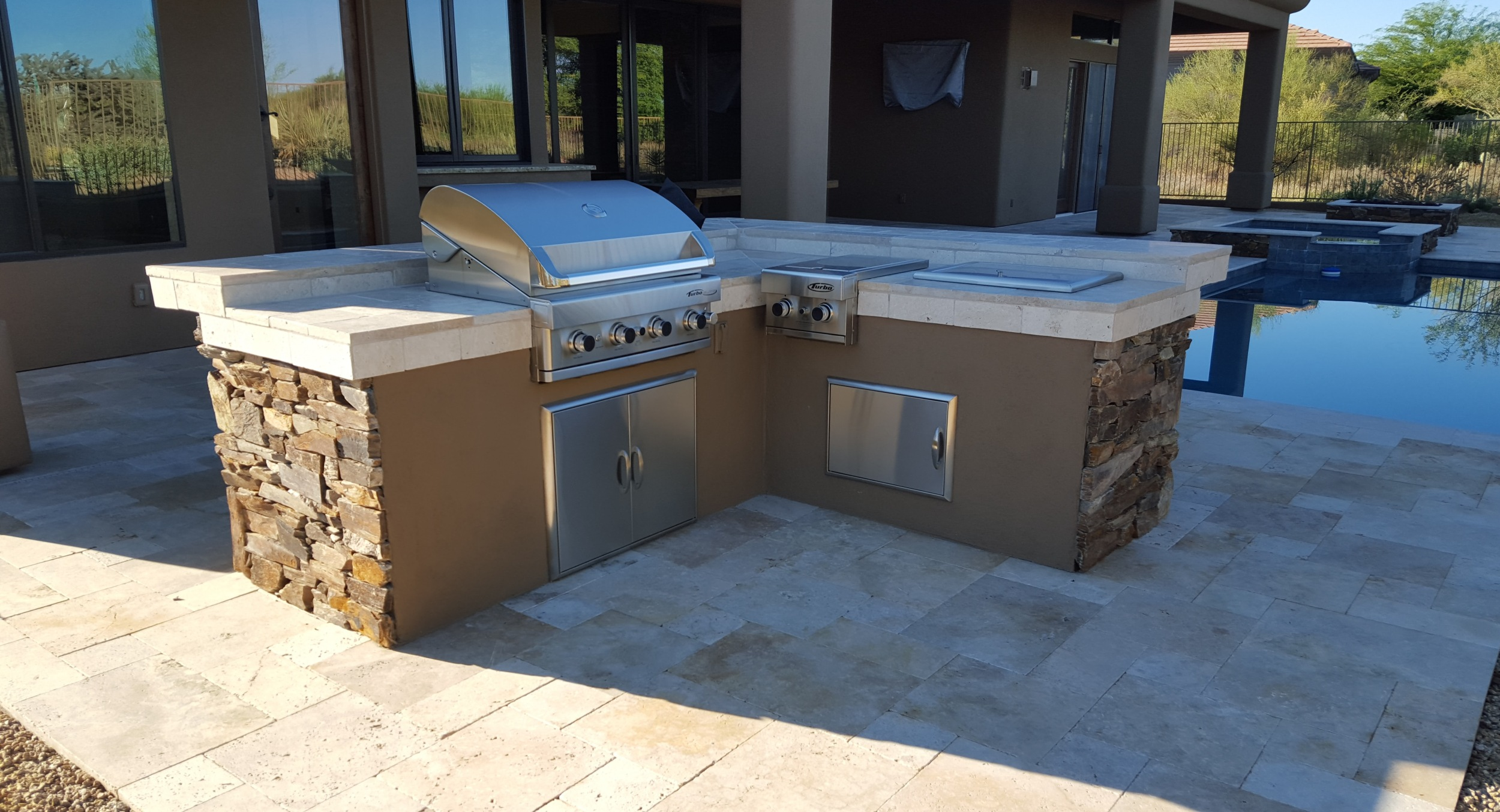 This built-in gas grill Scottsdale clients had us install on their new patio is a great looking combination of rustic stone facing, stucco, and a travertine counter. The wrap around bar is on the pool side of the unit.