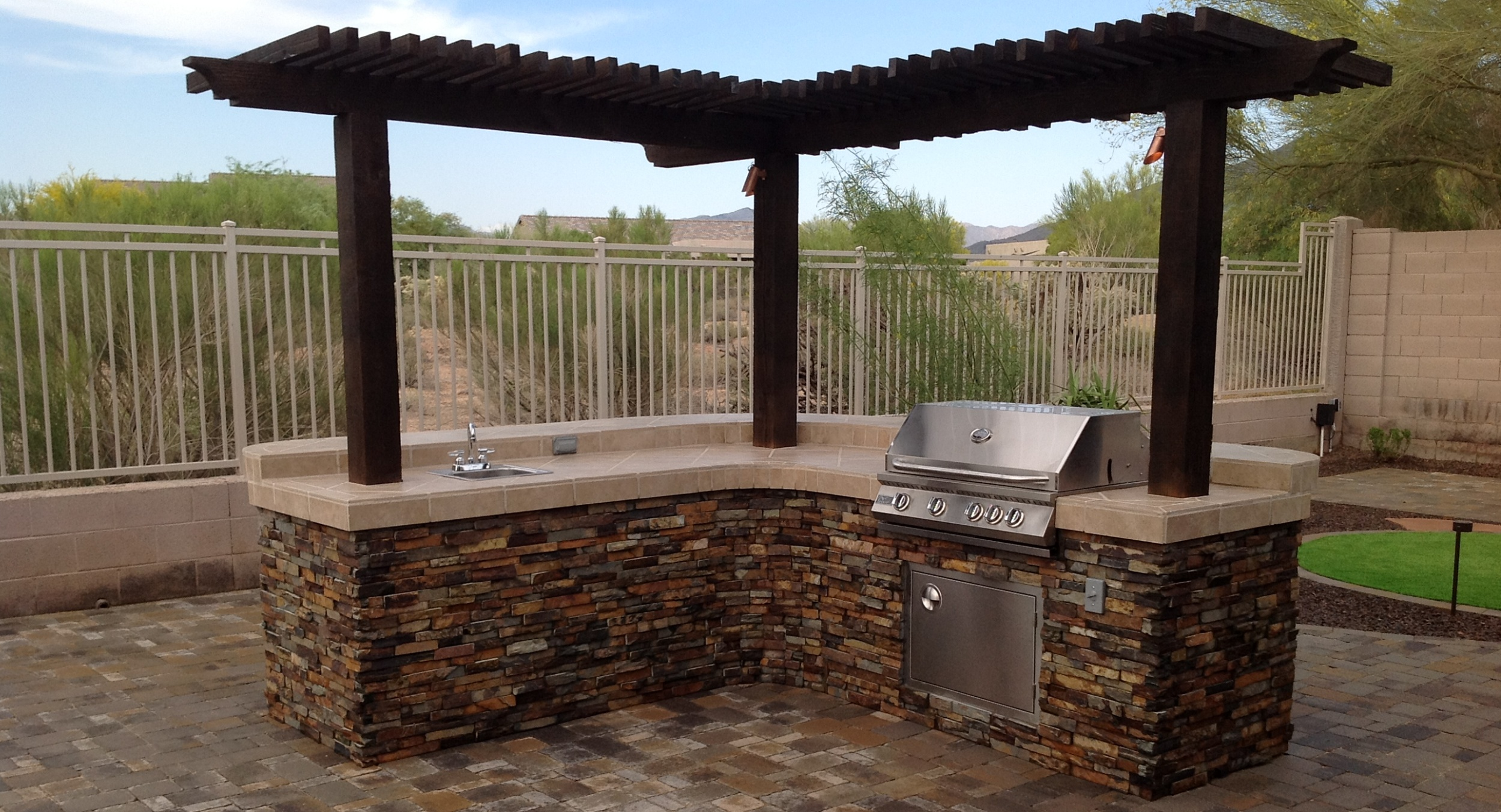 A gorgeous built-in grill Glendale, AZ clients had us build from natural stone with a coordinated tile counter topped with a mini ramada that creates shade and lights the space after dark.