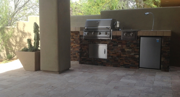 Even condo owners want a built-in grill. Phoenix landscaping clients now enjoy cooking out on this stone and travertine design we built on their covered porch.