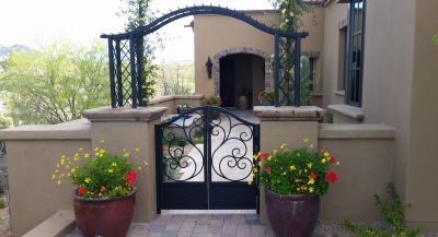 The entry to a lovely desert entry garden courtyard design. Scottsdale clients now welcome guests throu an iron gate under an arch covered with yellow Lady Banks roses.