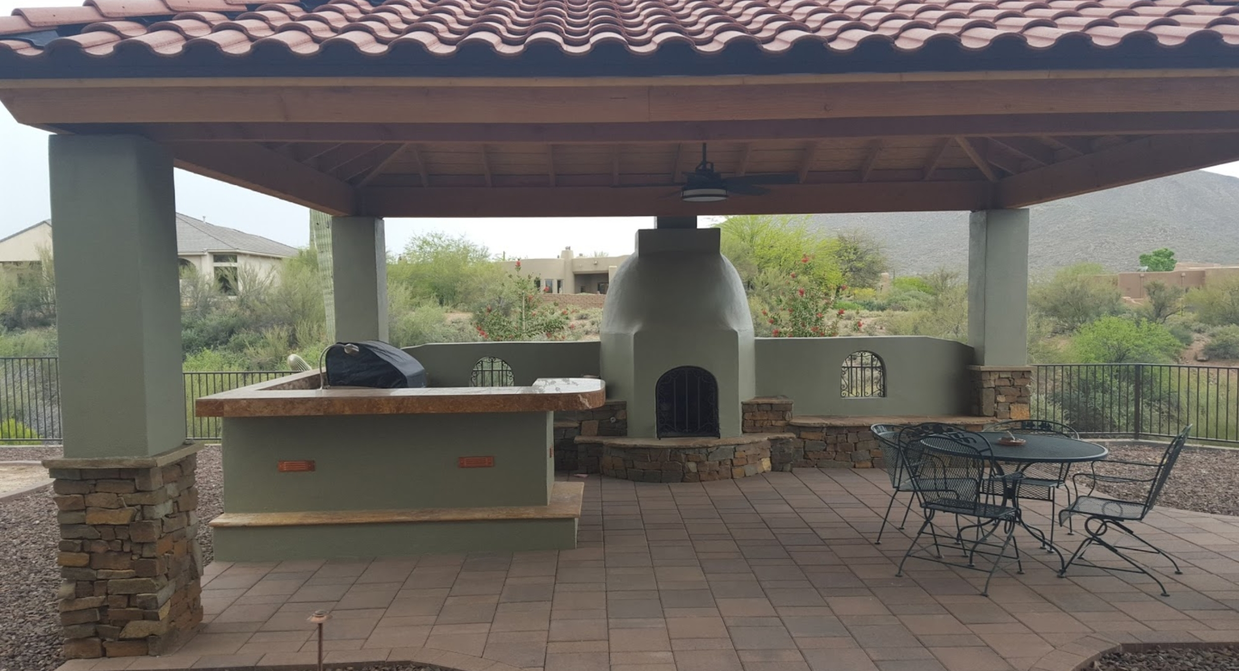 Soft silver green stucco shade structure with a red tile roof shelters the chef and diners in this outdoor kitchen and dining space.
