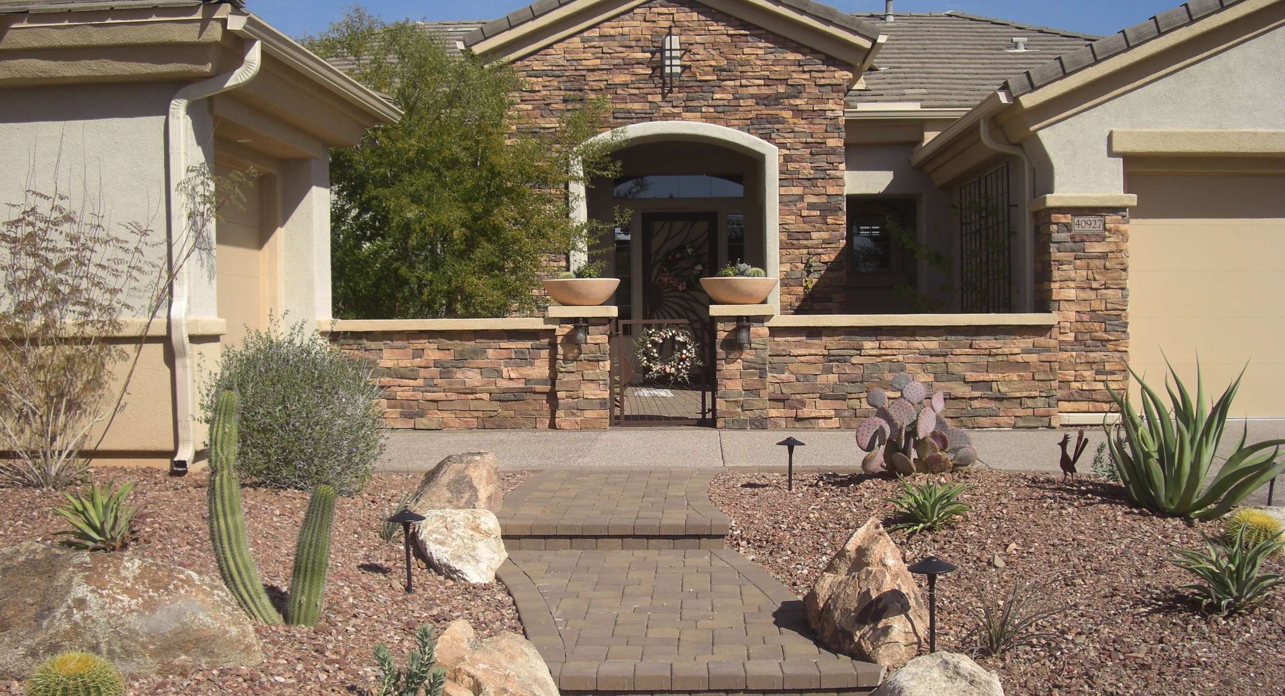 Welcome guests to your homw in style with handsome Phoenix courtyard designs like this one with walls of the same stone on the house entryway.