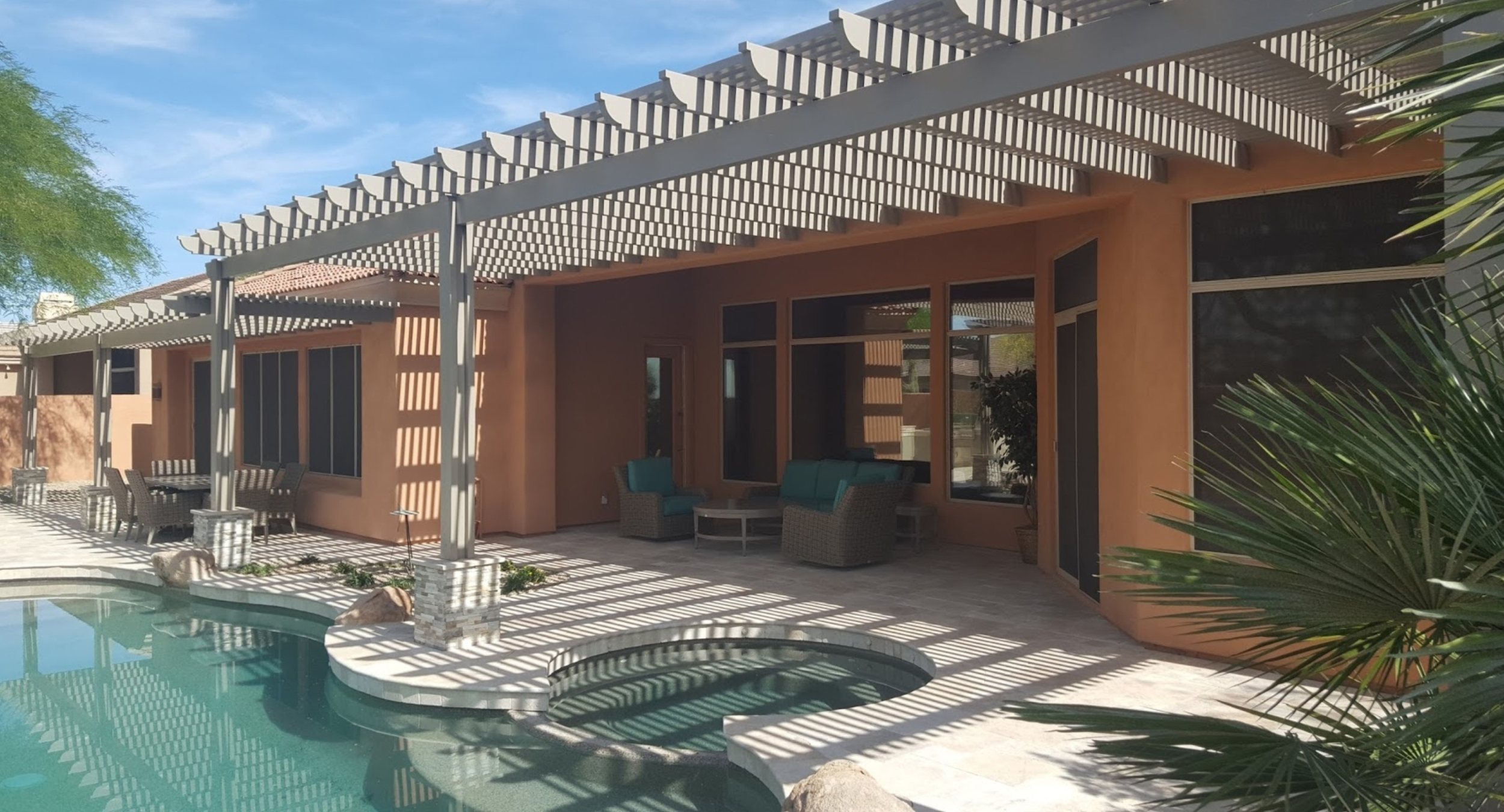 This Phoenix landscape design transformed a drab backyard into fab with a travertine patio-pool deck and an aluminum pergola that runs the full length of the house.
