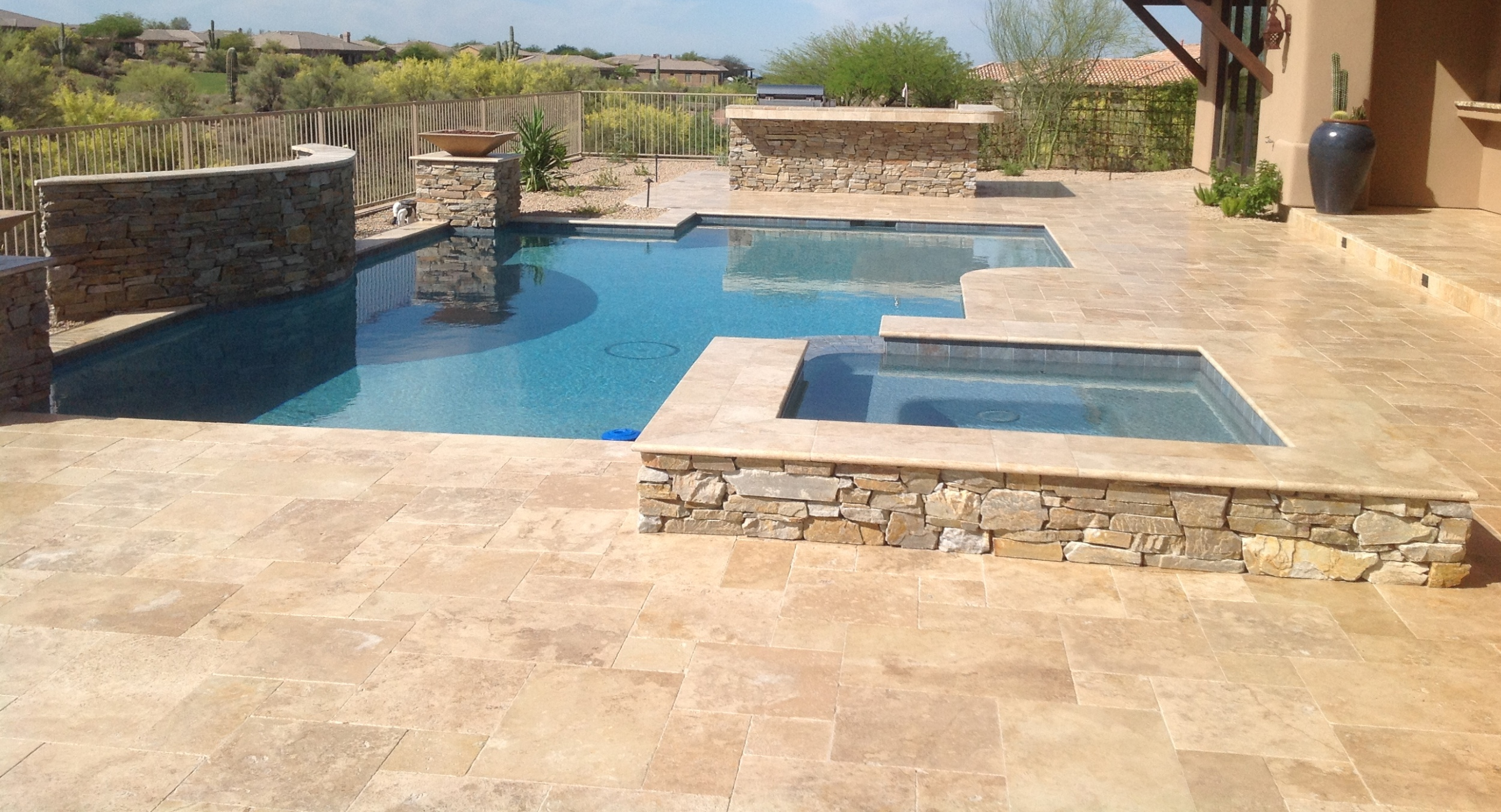 You've got lots of options for pool decking, Scottsdale, like this gorgeous golden travertine in this image. We do tile, stone, and pavers on all our Scottsdale - Phoenix pool decks.T