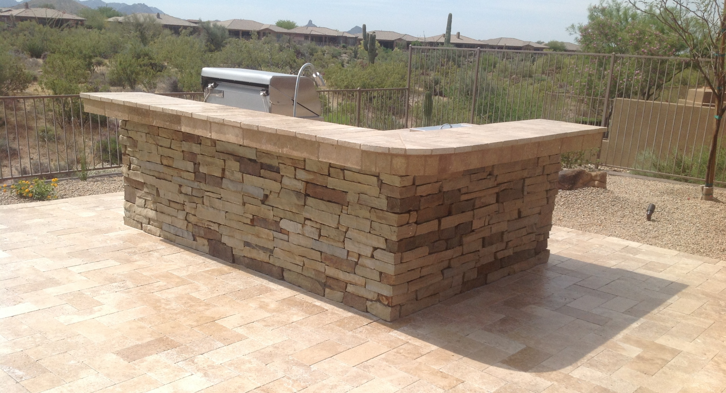 Entertain a lot? Consider the asset of having a Scottsdale built-in BBQ with a wrap around bar that seats 6 and doubles as serving space. A lovely natural stone design.