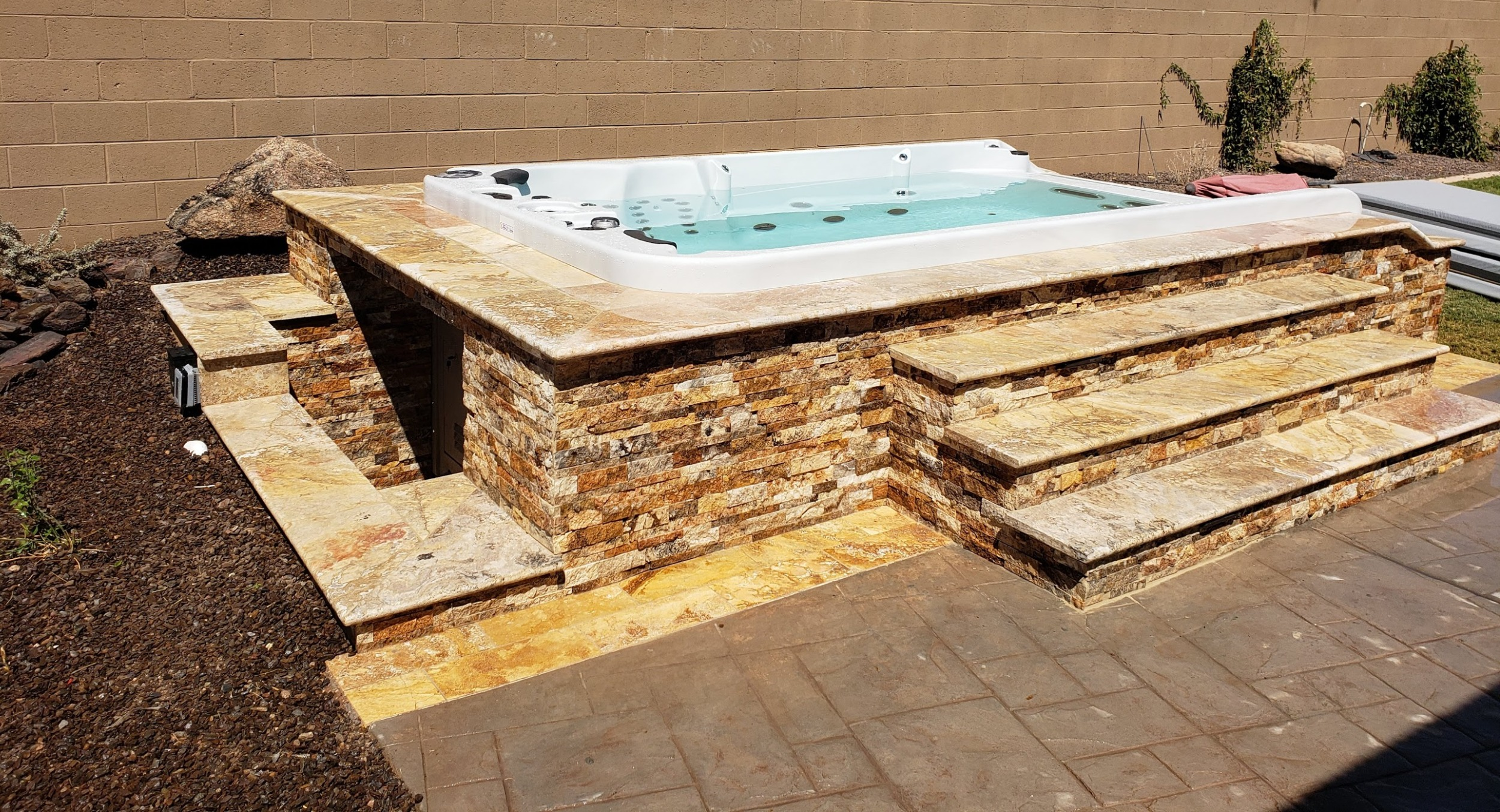 Natural stone is the way to go! This Anthem, AZ travertine spa surround is beautiful, and just the solution to hiding a 14-foot swim spa in plain site.