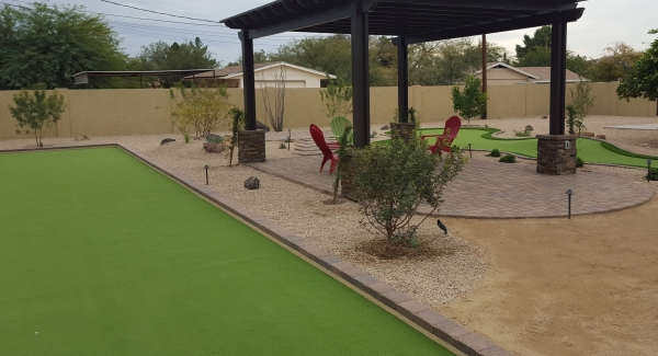 We replaced a huge bare area of wasted space for these clients with a backyard bocce ball court. Scottsdale synthetic grass was also used for a putting green on the other side of this shade ramada with a fire pit.
