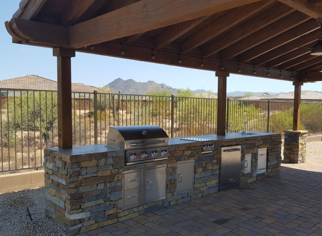 This gorgeous Cave Creek outdoor kitchen design backs up to the open desert. Dark split-face stone cabinet with the same stone uses in a polished tile top. All the stainless steel appliances and storage drawers create a wonderful combination of rustic and sleek.