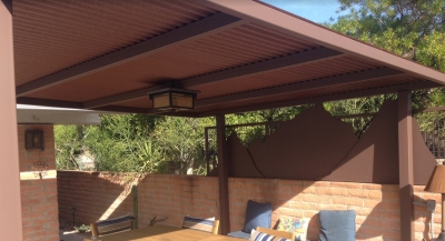 Go rustic modern with a corrugated steel shade roof. Phoenix landscape design clients had us paint this the color of rusted metal. Looks great with light red brick walls.