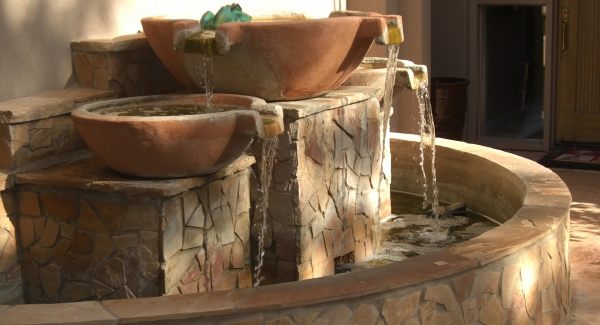 In the courtyard or on the back porch, Glendale landscaping water features are a welcome addition. This mosaic stone veneer and terracotta spill-pot design is perfect against the wall in a small space.