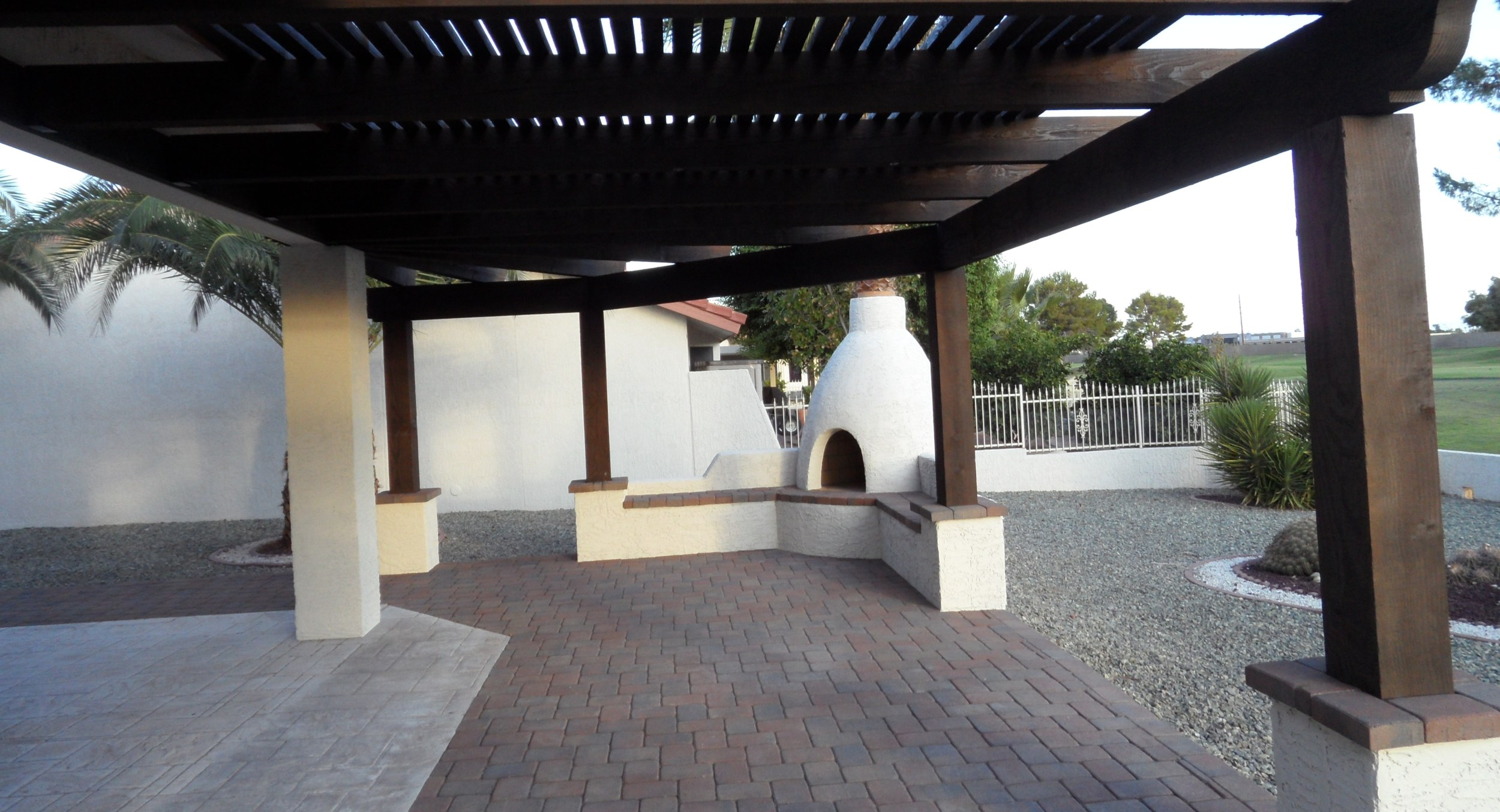 These Glendale, AZ landscaping clients wanted outdoor living space improvements. They now have extended the patio with dark pavers. Additionally, all the new entertaining space is under a big shade ramada, and they've got a new beehive outdoor fireplace too.