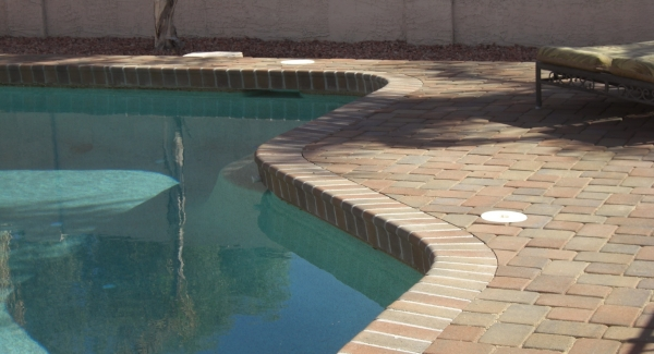 Got old pool decking that has seen better days? Desert Crest remodels Glendale, AZ pool decks with pavers and stone. This client's remodeled decking is now pavers with a matching bull nose edge that doubles as the decorative tile around the top of the pool itself. Very sleek and modern with natural appeal.