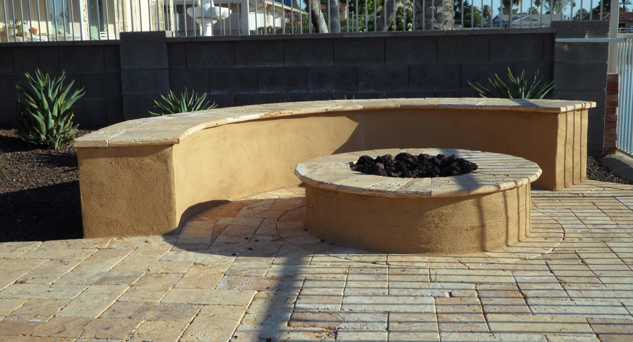 Matching the stucco seat wall and base to the predominant buckskin in the travertine patio made this outdoor fire pit's look outstanding. Far more of a focal point than if it was all stone-faced.