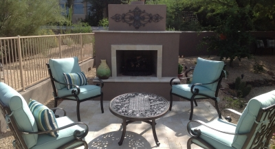 Scottsdale landscaping design for relaxing. This client's new outdoor fireplace is the focal point in their new patio space, dark stucco accented with light travertine from the patio paving and a lovely wrought iron piece on the chimney.