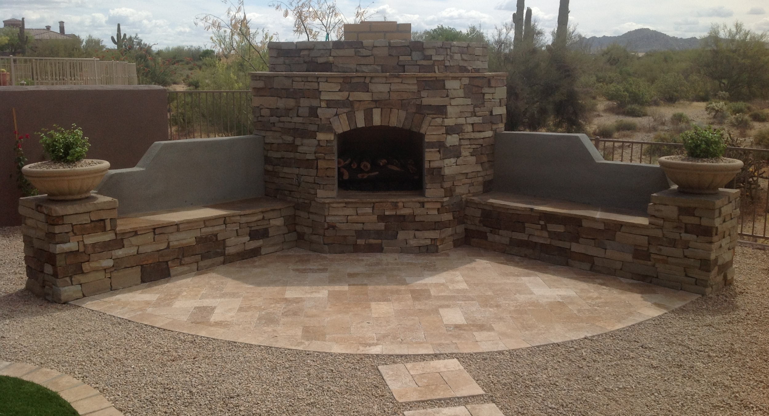 Stone and travertine combined make beautiful outdoor fireplaces. Scottsdale outdoor living spaces like this one will get lots of use for both relaxing and entertaining friends.