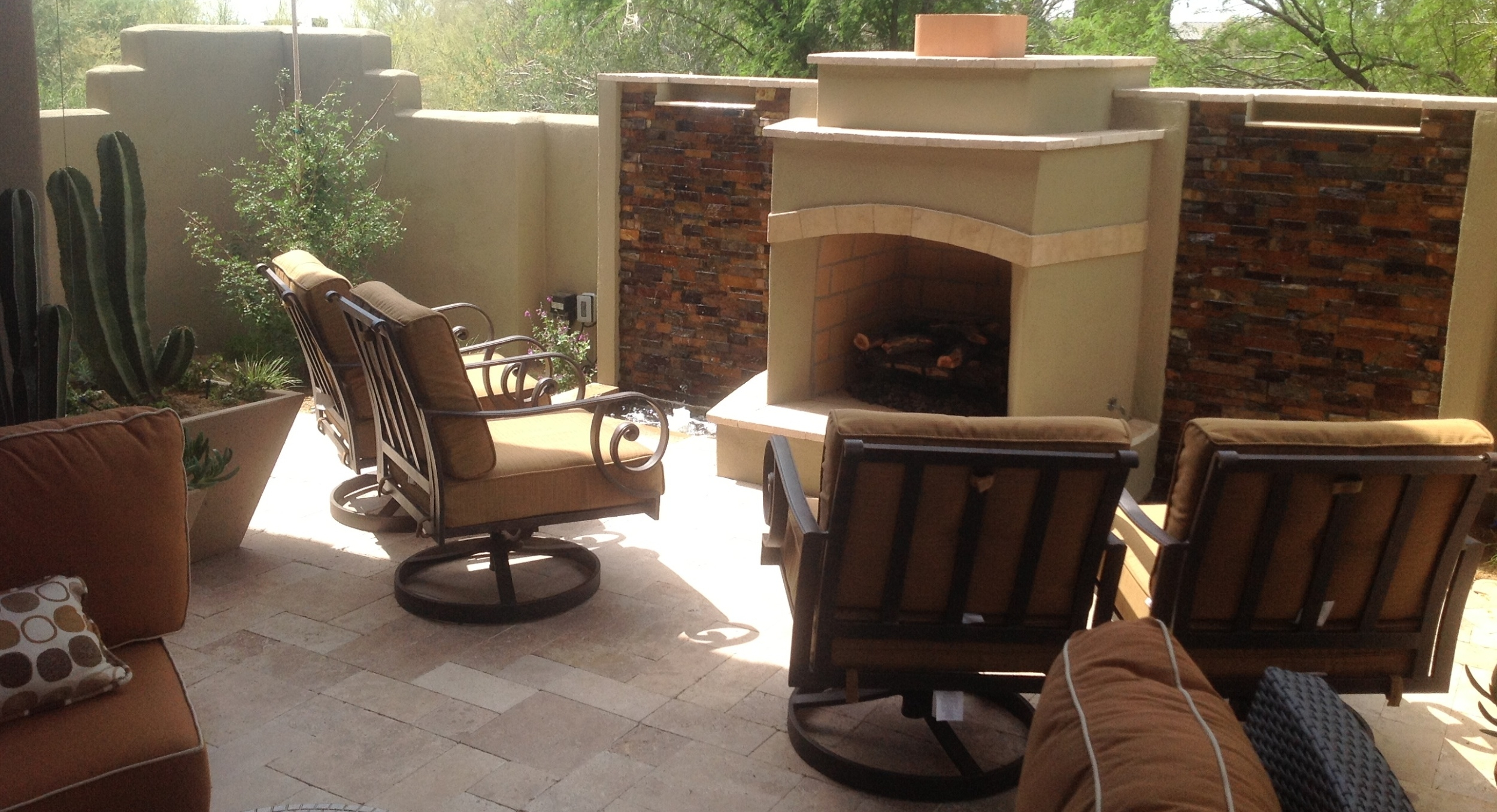 Combinging waterfalls with outdoor fireplaces allows you to have more outdoor living room features in very limited space. This client's condo porch and backyard are all one patio with this stone and stucco design against the private property line privacy wall.