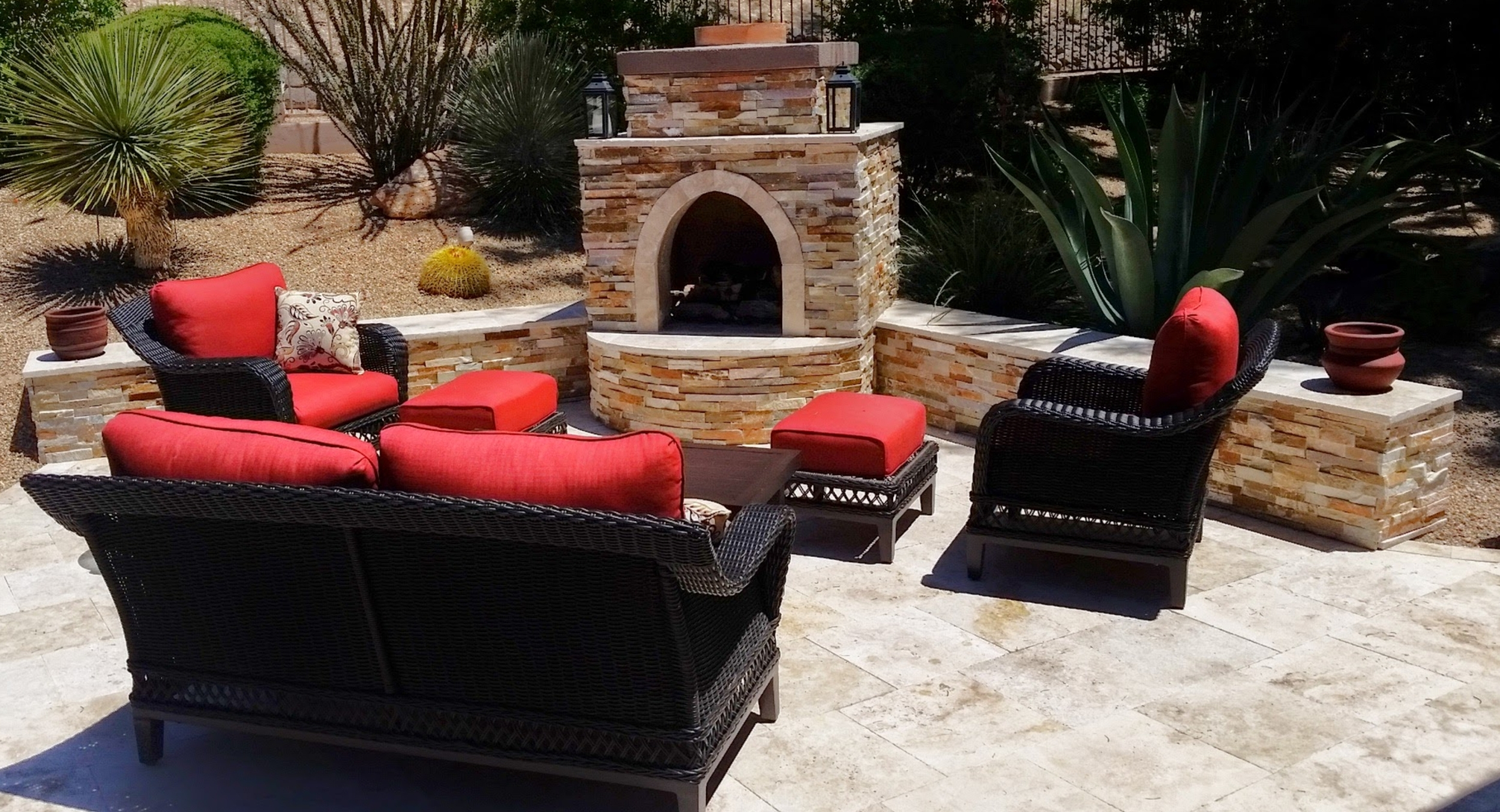 Patio landscaping is way more than a paved space today. We want it enriched with features, like this Phoenix outdoor fireplace made from the same travertine as the new patio as an accent to the Autumn Blend split-face stone veneer.