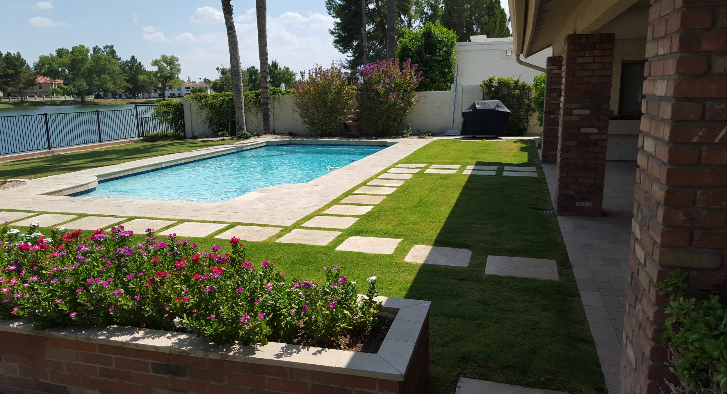 A totally changed backyard with the sod and pavers update swimming pool Scottsdale project completed. Very plush and modern without putting on airs.