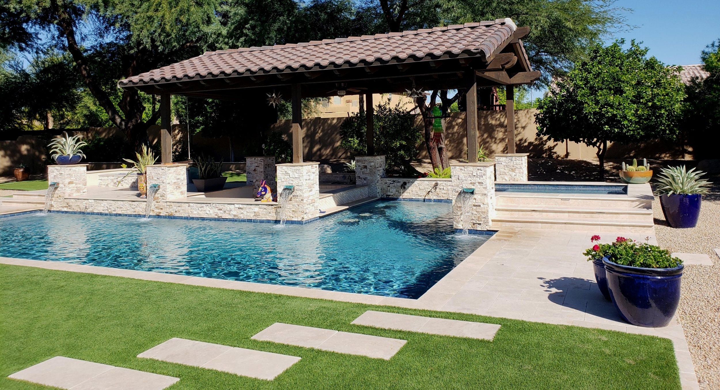 The pool is a huge player in your outdoor living space, Make it awesome with custom pool design. Peoria, AZ pool installation includes raised spa, swim bar, fountain wall and pillars, plus a timber ramada over the bar and underwater seating.