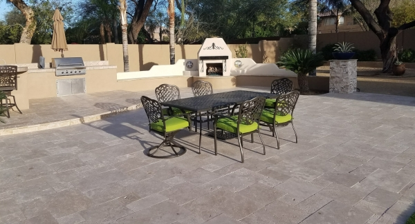 Swimming pool construction called for removing part of the old patio, so an update to the outdoor living space's floor came next. Peoria patio design useing light travertine pavers turned a very nice backyard into gorgeous.