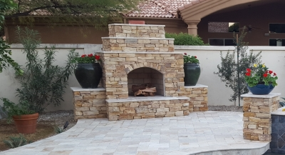 For their new poolside outdoor fireplace, Scottsdale clients selected stone veneer that echoed the colors of their travertine patio in reverse. So, it stands out from all the white around it, yet doesn't overcome the light, airy feeling.