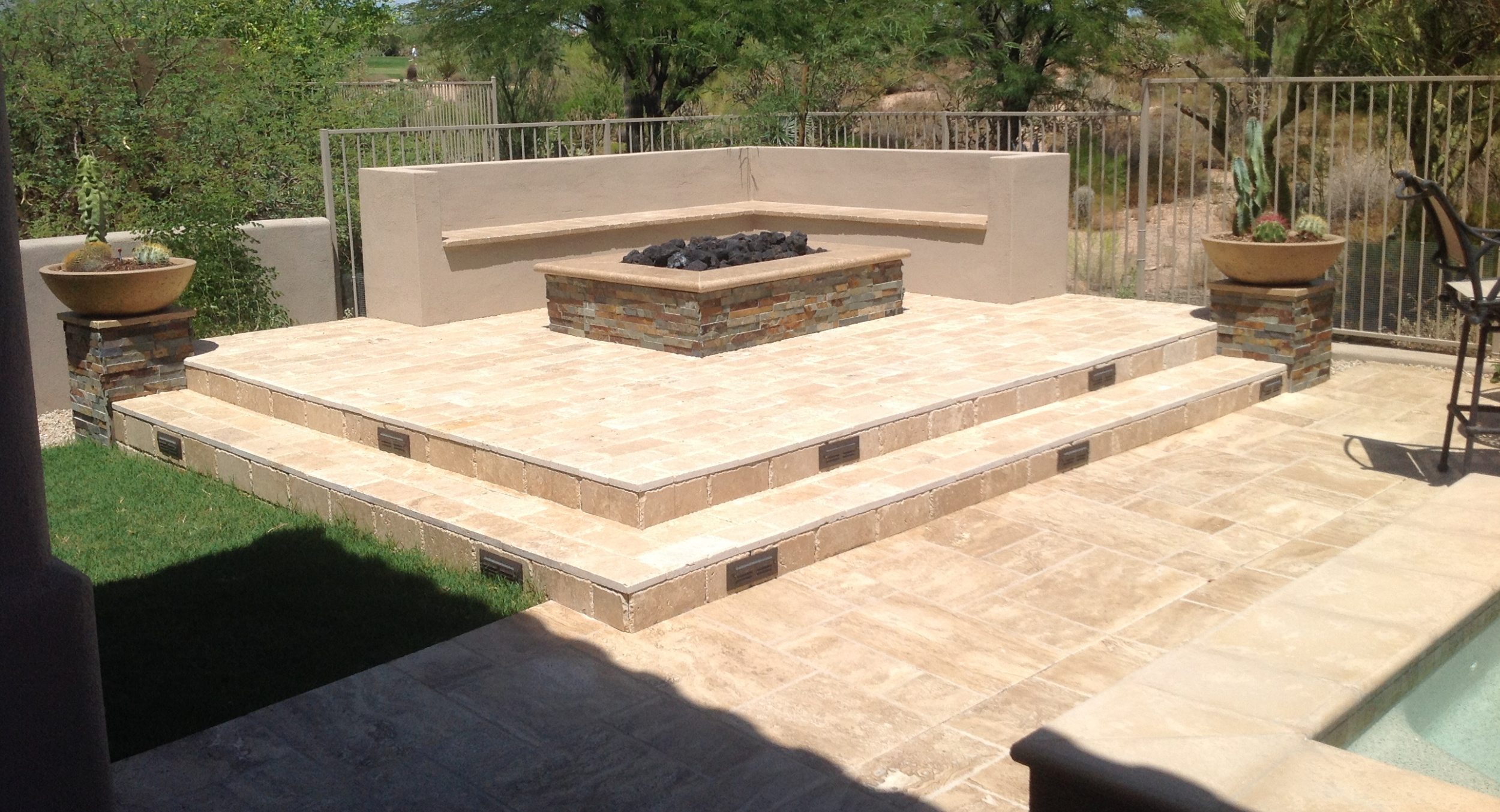 Get lots of aesthetic impact from raised gas fire pits. Scottsdale patio upgrades with travertine and split-face stone aren't something you want to hide.