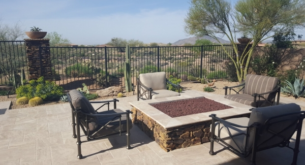 A gorgeous travertine patio might seem out of step with rustic stone fire pits. Anthem patio design done to be at one with the untamed desert turns the pairing into a beautiful air of rustic elegeance. The rough-faced stone is also used on fencing pillars, pool fountain pedestals, and the pool spa's walls. with highlights of rustic elegance.