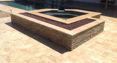 Cool combination on a pool we remodeled in Scottsdale; fire pit spa surround. Stone and travertine, a lovely pool deck attraction.