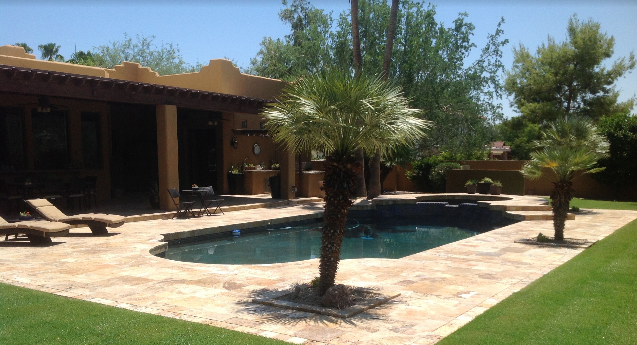 Rich-colored new travertine paving refreshed this whole backyard. Gorgeous Scottsdale pool deck remodel included replacing the lawn with fresh sod too.