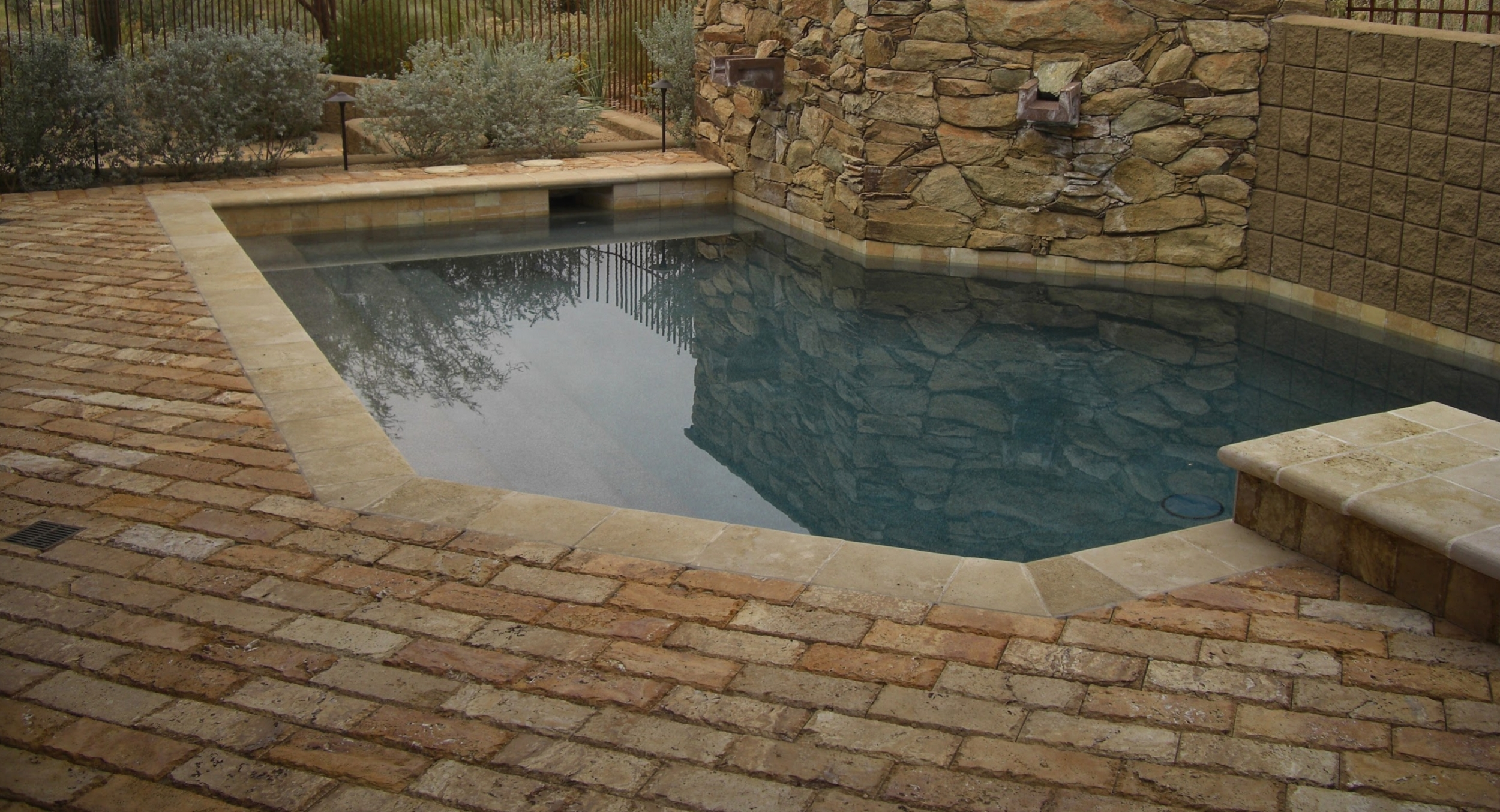 A gorgeous backyard even though it's small and has little room for landscaping. In Scottsdale, pool decks like this one are part of awesome outdoor living spaces. It's paved with dark, chiseled travertine brick to match the pool water feature and porch pillars..
