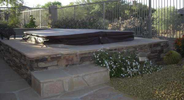You've got color and style options for any of your natural stone spa surrounds. Peoria, AZ clients had us use darker stone on the sidewalls as a striking accent to the patio's flagstone, which we used to cap off the partially submerged spa's seat deck..