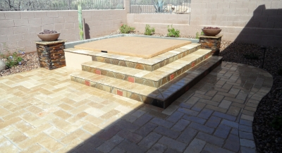This outstanding Scottsdale spa surround's done in Noche Travertine and Autumn Blend flagstone. The step riser lights have copper fixture covers to blend best with that dark flagstone.