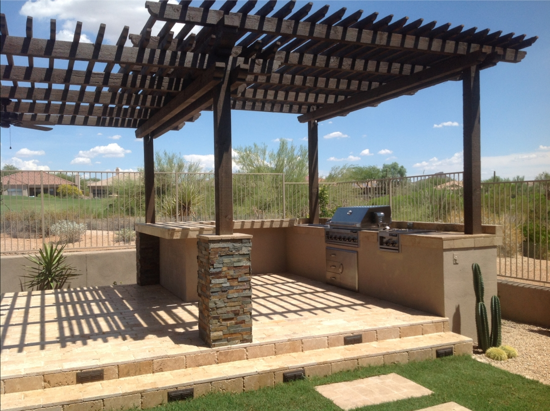 This unique split-level wood pergola features overlapping slat roofs at different heights. An interesting element for Scottsdale patio design. Not only is the dark stained wood posts and trellis roof great looking, the overlap doubles the shade in the bar area.