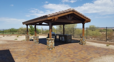 A gorgeous dark brown rustic ramada with a tile roof occupied one corner of a large paver patio. Beneath the shade structure is a spacious patio dining area and a well-equipped outdoor kitchen. Cave Creek design by Desert Crest.