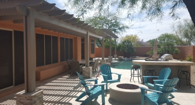 There's all kinds of amenities in this small backyard where the travertine Phoenix patio design and pool deck combine into one beautiful outdoor living space with a built-in gas grill,, gas outdoor fire pit, and a new shade pergola that runs the full length of the house.