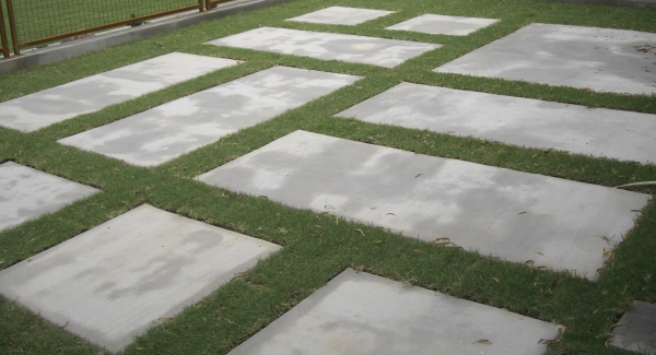 A little grass can carry a lot of weight, like this small strips of Phoenix lawn between large concrete stepping stones.